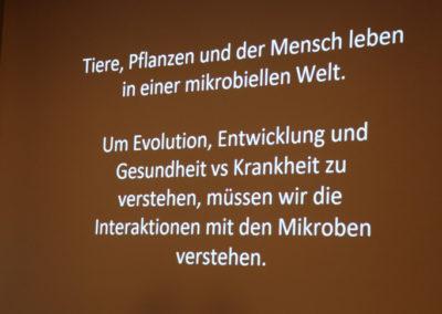 """Scrennshot von der Präsentation: """"Tiere, Pflanzen und er Mensch leben in einer mikrobiellen Welt. Um Evolution, Entwicklung und Gesundheit vs Krankheit zu verstehen, müssen wir die Interaktionen mit den Mikroben verstehen."""""""