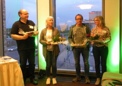 4 Personen stehen nebeneinander mit Geschenken in der Hand