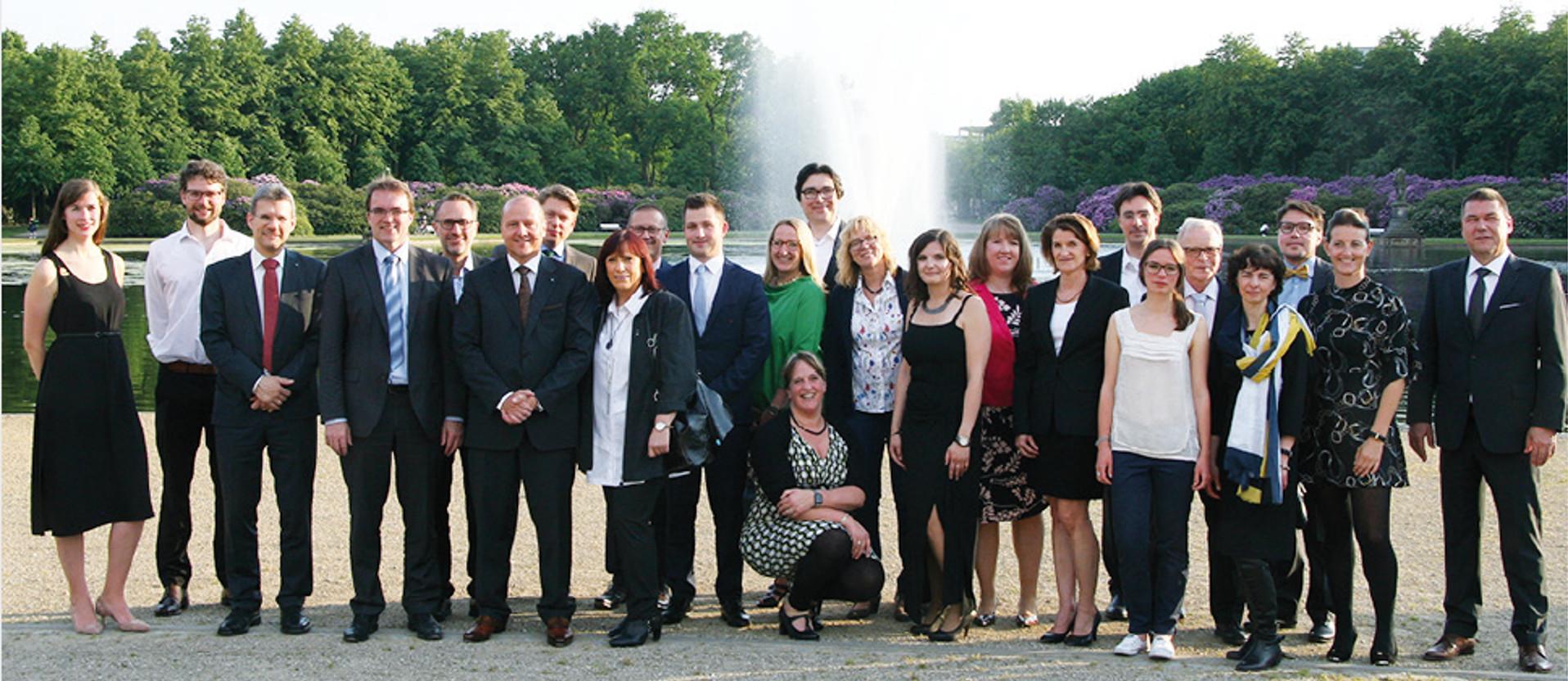 Eine Gruppe aus vielen Personen vor einem Springbrunnen und grünen Bäumen