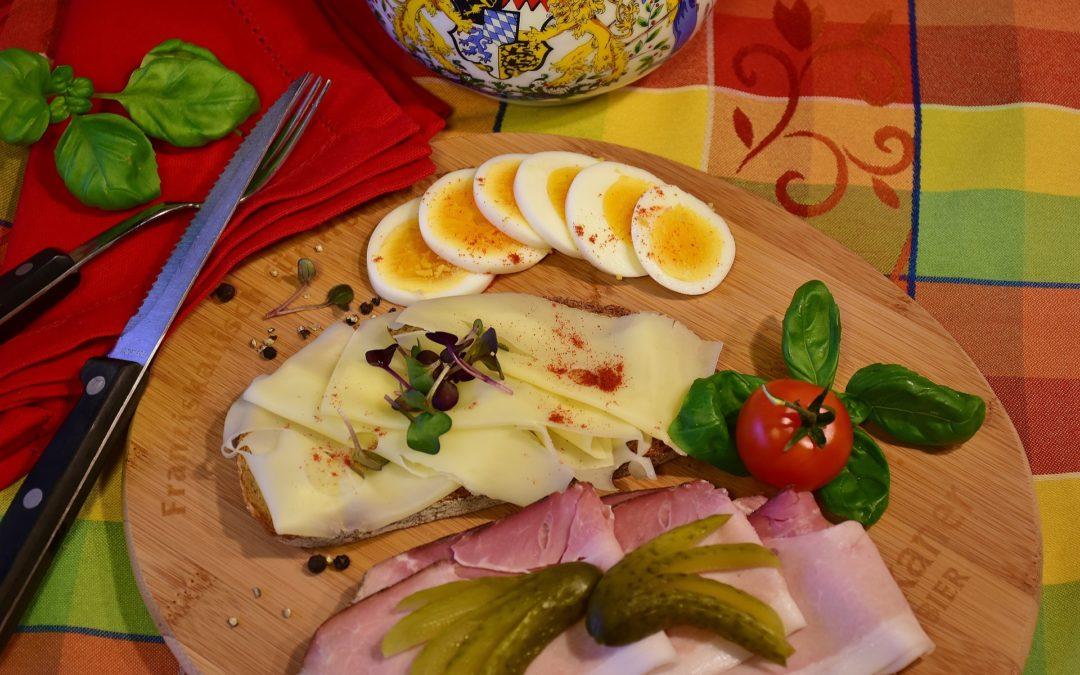 Brotzeit mit Brot, Kochschinken, Käse und Ei, mit Gurke und Kräutern garniert
