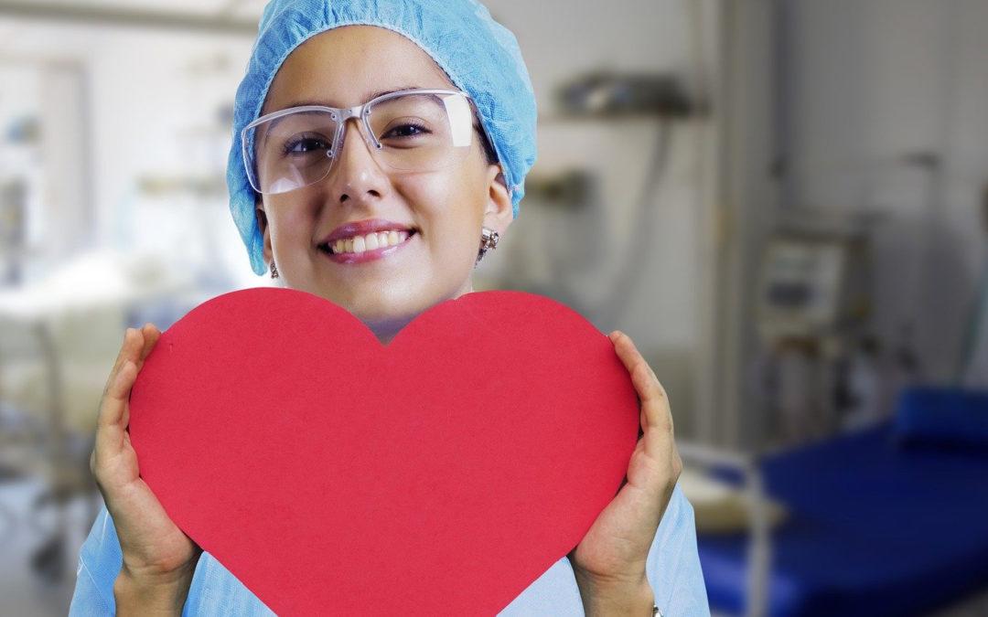 Foto einer Pflegefachkraft mit großem rotem Pappherz in den Händen