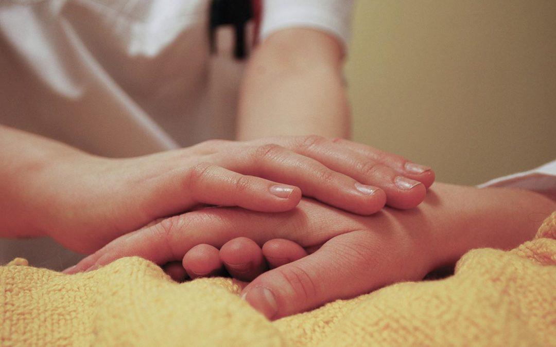 Jemand hält die Hand einer liegenden Person in seinen Händen