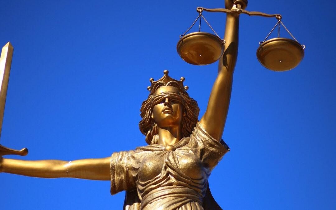 Justitia-Statue vor leuchtend blauem Himmel