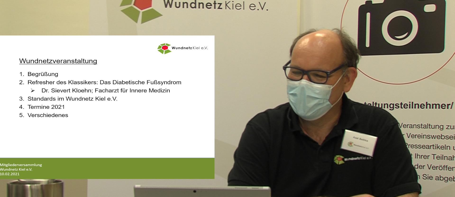 Mittelalter Mann mit Brille, Glatzenansatz und OP-Maske am Laptop. Im Hintergrund die Präsentation.