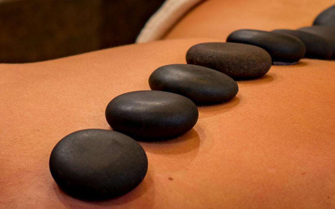 Ebenmäßige schwarze Steine, die entlang der wirbelsäuöe auf einen Rücken aufgelegt wurden.