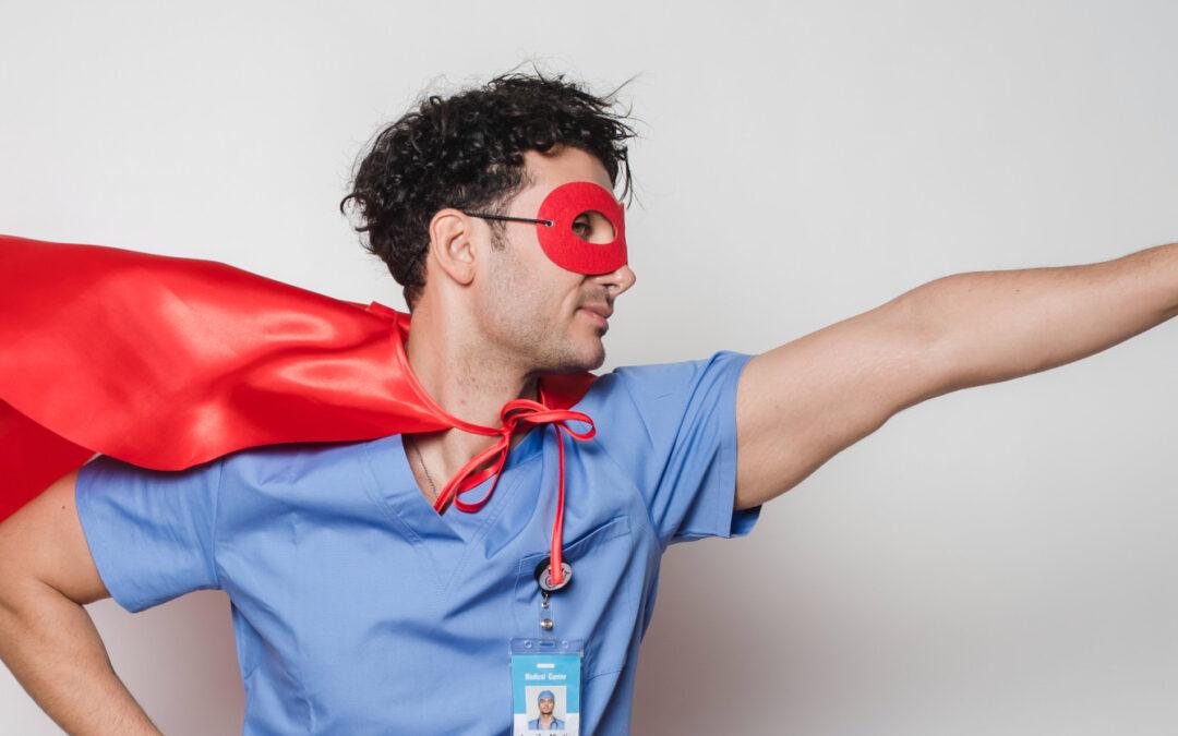 Ein Pfleger, der einen roten Umhanf und eine Maske wie Superman trägt.